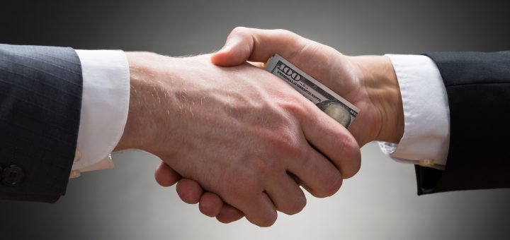 Close-up Of Two Businesspeople Shaking Hands With Money